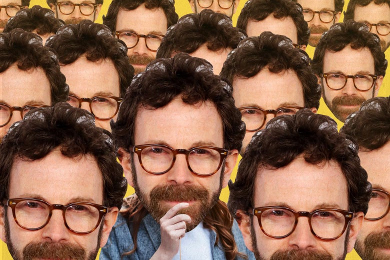 A person holding up a cutout of Charlie Kaufman's head over his own, surrounded by other images of Kaufman's head.