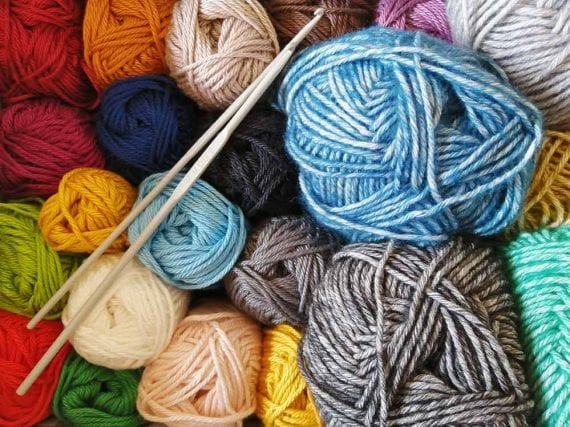 A craft shop that sold yarn, needles, and patterns could suggest knitting.